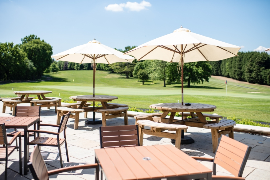 The spacious terrace with a beautiful green view over the golf course - a perfect back drop for your wedding photos .